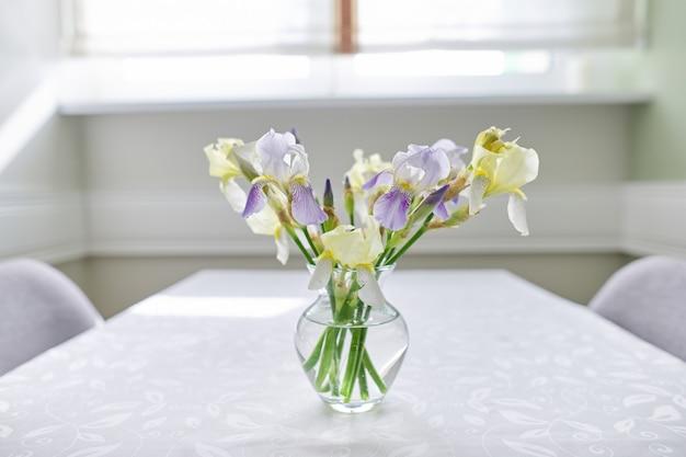 窓の近くのテーブルに黄色と紫の菖蒲の花束と花瓶