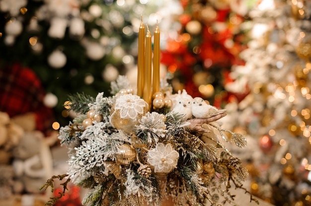 Vase with christmas decor composition of flowers and candles