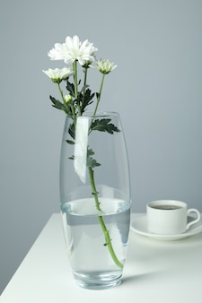 Vase with chrysanthemums and cup of coffee on white table.
