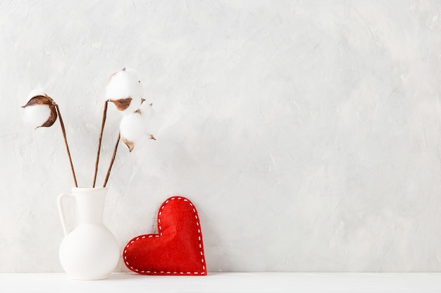 A vase with cotton and a red heart against the of a light wall, a concept, a postcard for valentine's day.
