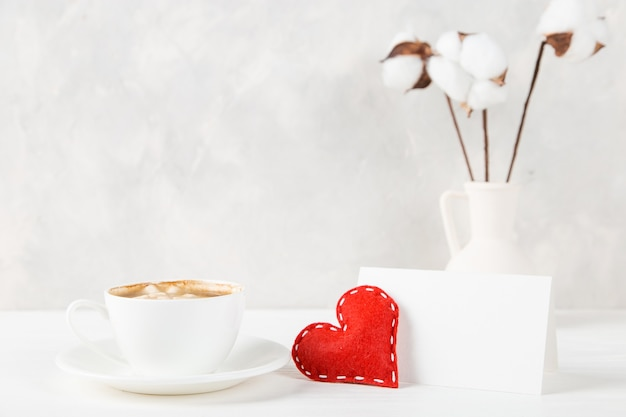 A vase with cotton, red heart, morning coffee against the of a light wall, concept, a postcard for valentine's day.