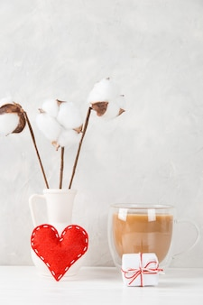 A vase with cotton, red heart, morning coffee and a gift against the of a light wall, concept, a postcard for valentine's day.