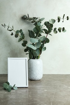 Vase with eucalyptus branches and photo frame