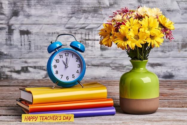 꽃과 노트북 꽃병입니다. 나무 배경에 다채로운 노트북입니다.