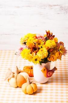 テーブルの上に花と小さなオレンジ色のテキスタイルカボチャが付いた花瓶