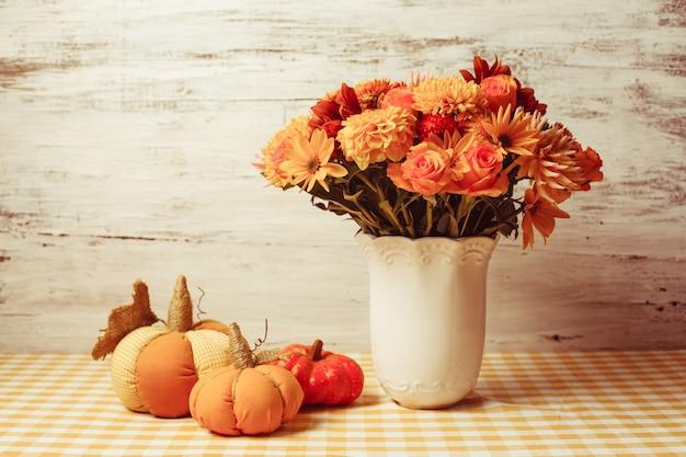 테이블에 꽃과 작은 주황색 직물 호박이 있는 꽃병