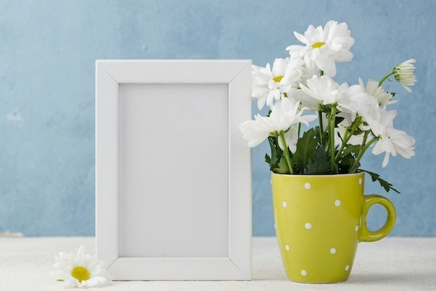 Vase with flowers beside frame