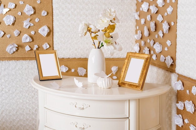 Vase with flowers and photo frames on a table in white and golden bedroom. still life, room decoration details.