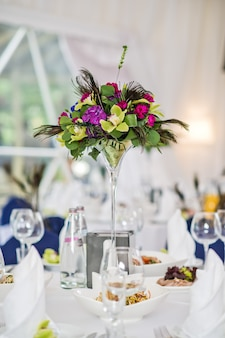 Vase with flowers on a served round table, dinner in a luxurious restaurant