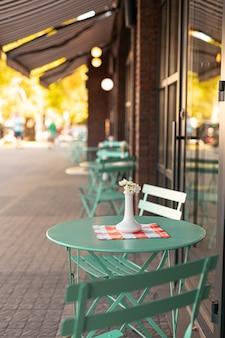 Ваза с живыми цветами на салфетке, украшает стол уличного кафе.