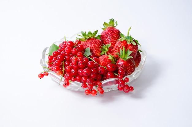 白い背景、上面図にイチゴと赤スグリの果物と花瓶。