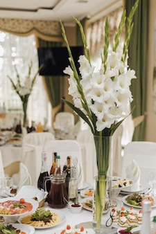 Vase with iris flowers stands on the table with food in a restaurant