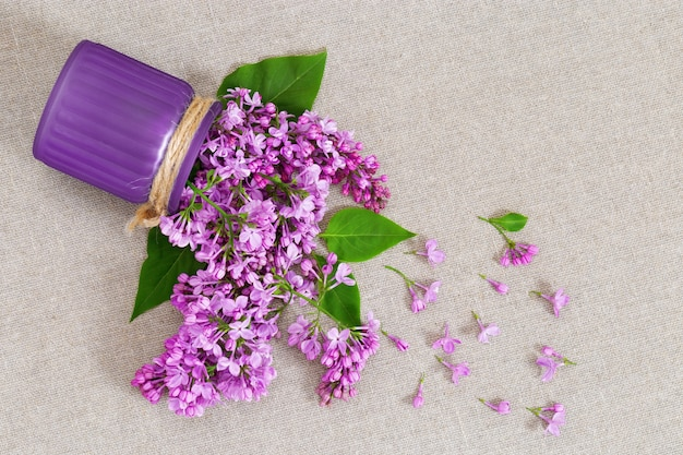 Vase with lilac flowers scattered on natural rough material.