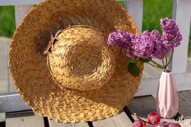 Vase with a lilac and a hat stand at the fence on a wooden floor