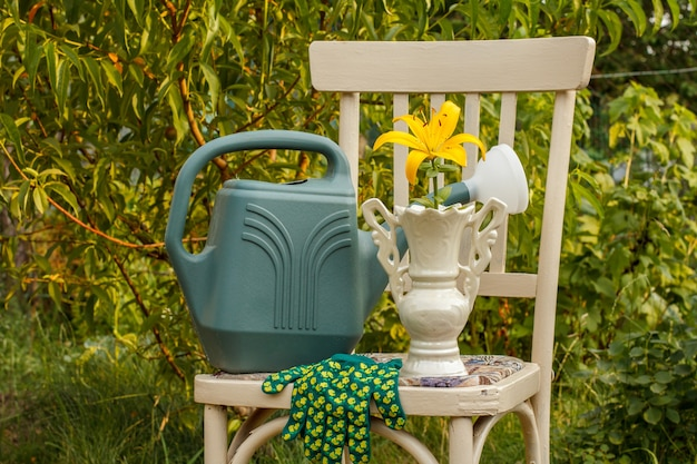 Vase with lily flower, watering can and glove on old chair staying in the garden in summer day.