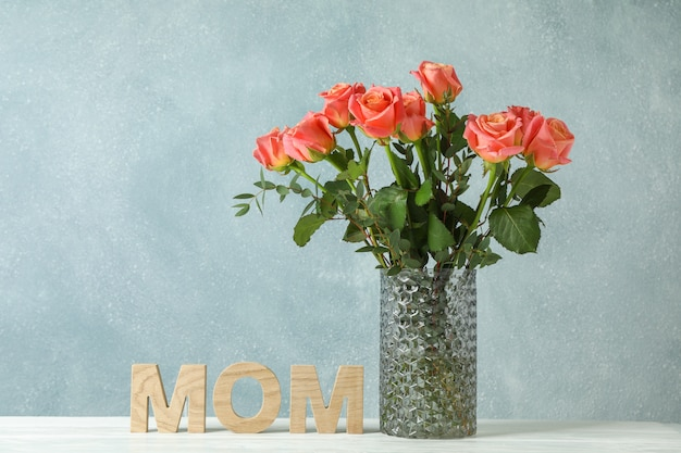 Vase with orange roses and inscription mom on white table
