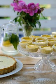 牡丹の花と夏の木製のピクニックテーブルのレモネードとデザートの花瓶。家族の休日。