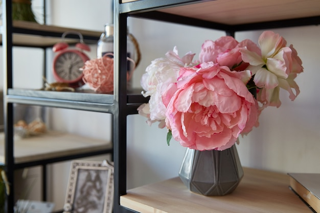 A vase with pink flowers with stands alarm clock on a shelf in the room.