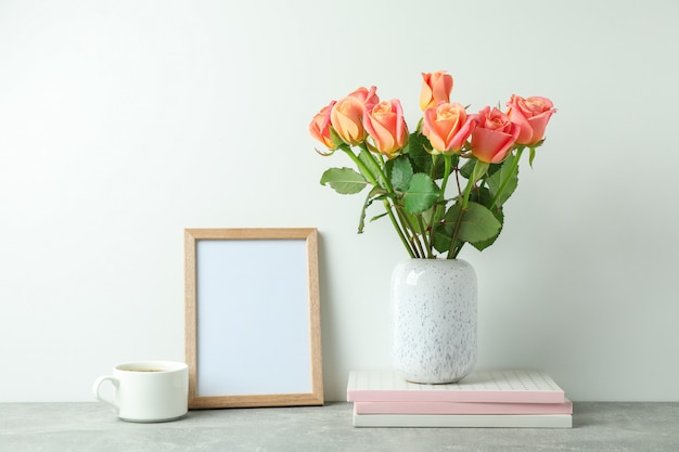 Vase with pink roses, copybooks, empty frame, cup of coffee on grey table