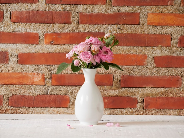 Vase with pink roses on white table near brick wall