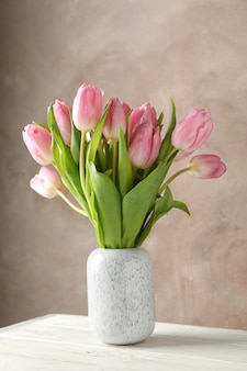 Vase with pink tulips against brown background, space for text