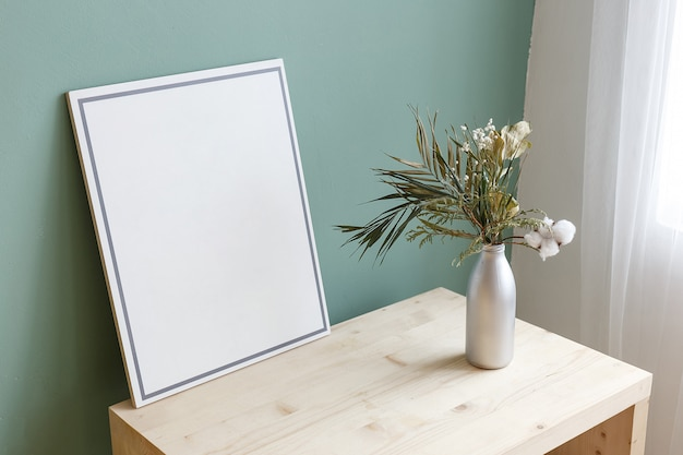 Vase with a plant on a table near a picture with copy space.