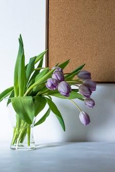 紫色のチューリップの花と木の板が付いている花瓶。コピースペース