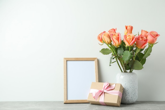 Vase with roses, gift and empty frame on grey table