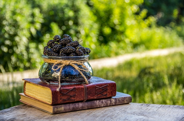 Vase with summer berries and stack of books.