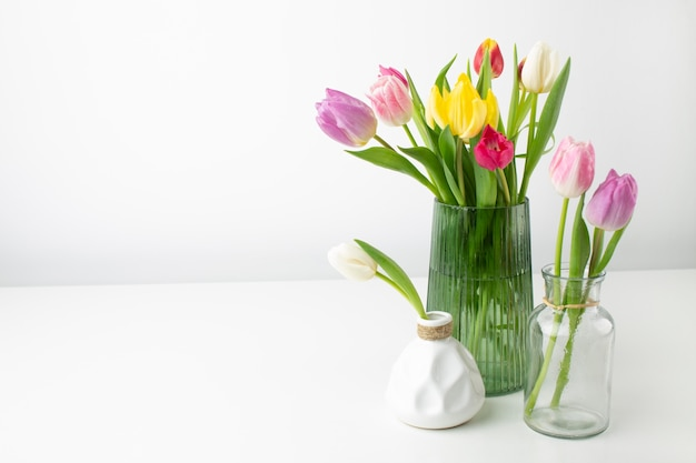 Vase with tulips on table