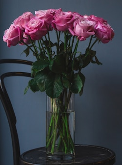 A vase with water and pink roses inside