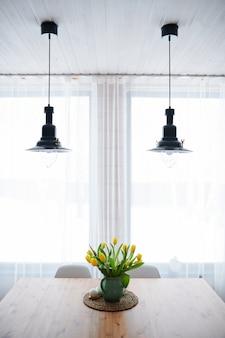 木製のテーブルに黄色のチューリップとリビングルームの窓の上にぶら下がっている2つのランプと花瓶