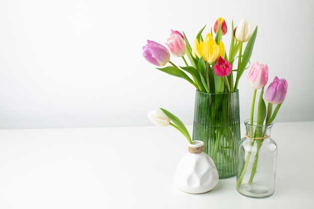 Vases with flowers on desk