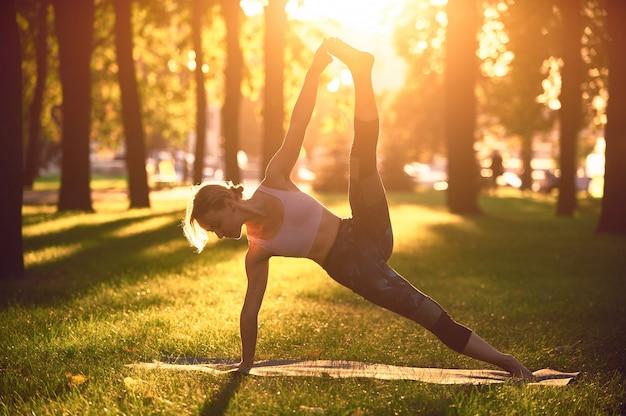 美しい若い女性は、夕暮れ時の公園でヨガの高度な側板ポーズvasisthasanaを練習します