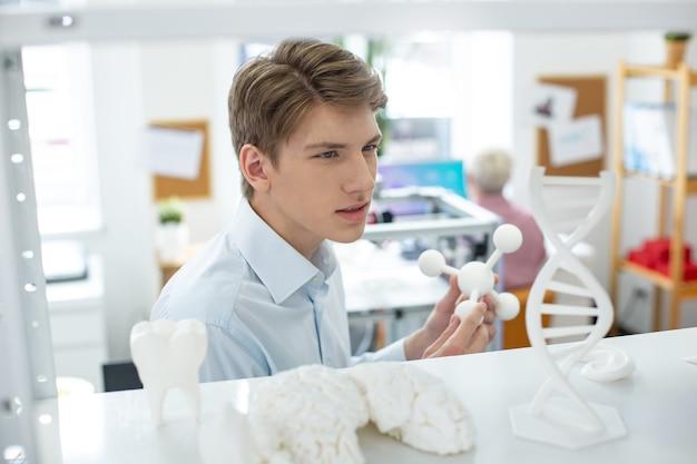 방대한 컬렉션. 3d 프린터로 인쇄 된 모델을 들고 전체 컬렉션으로 선반을 검사하는 매력적인 젊은 남자