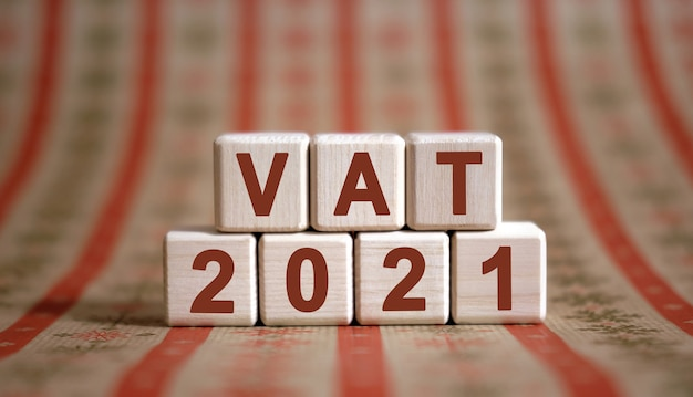 Vat 2021 text on wooden cubes on a monochrome background with reflection.