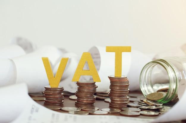 부가가치세 개념 단어 부가가치세는 쌓인 동전과 유리병에 동전을 넣은 나무 탁자 위에 올려 놓았습니다.