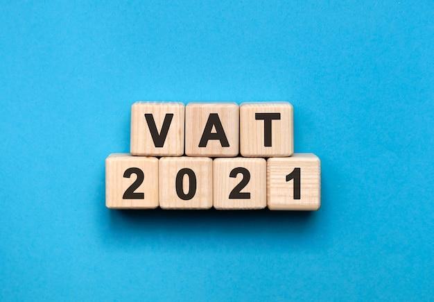 Vat-グラデーションの青い背景を持つ木製の立方体のテキストの概念
