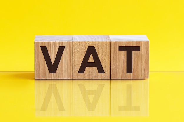 Vat on wooden cubes over blur background with copy spcae, financial concept background. yellow background