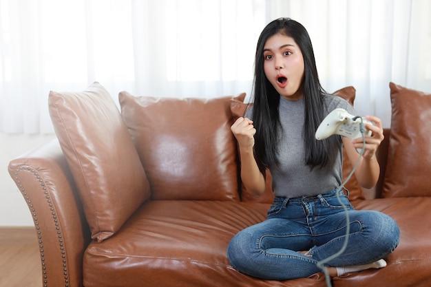 Концепция игровой консоли vdo. активная азиатская женщина сидит на диване, держит джойстик и играет в увлекательную игру