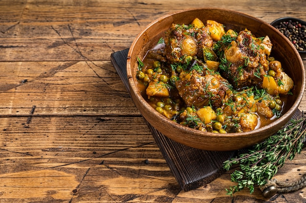 Тушеные хвосты бычьих хвостов из телятины с овощами в деревянной тарелке