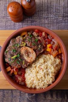 Телячья (говяжья) рулька с ризотто с шафраном в миланском соусе, гремолате и соусе.