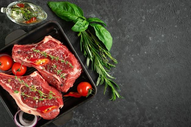 Биток из телячьей кости на сковороде для гриля с овощами, зеленью и оливковым маслом
