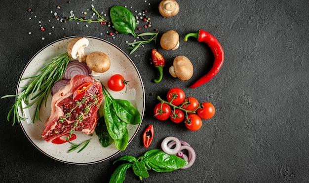 Биток из телячьей кости на тарелке с овощами, травами и специями. приготовление мяса. вид сверху, копия пространства.