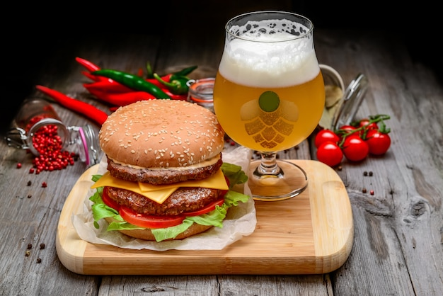 Veal burger with cheese and beer on wooden table