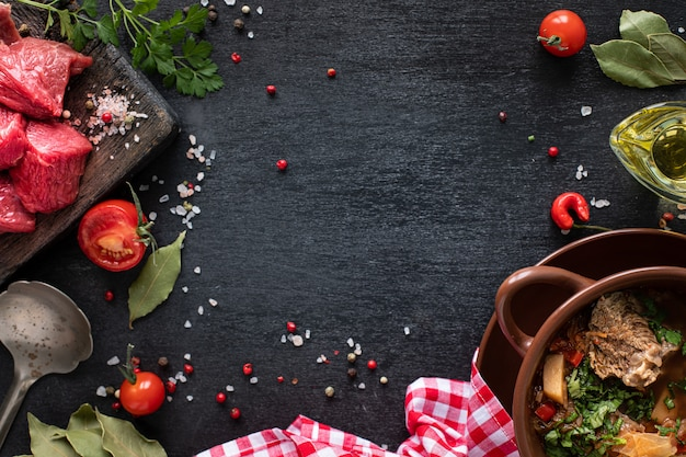 Veal fillet on a wooden cutting board with cherry tomatoes, hot pepper and herbs.