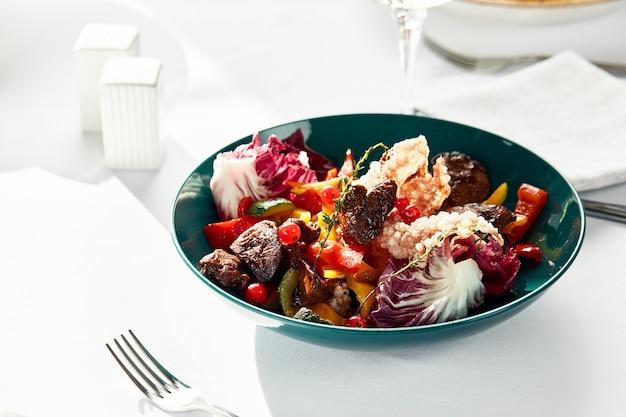 子牛のレバー、サラダ、マンゴー、オレンジスライス、クローズアップ、明るい背景、白い料理。