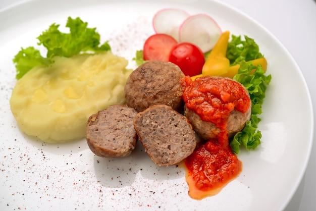 Тефтели из телятины с рисом и томатным соусом, на фоне картофельного пюре
