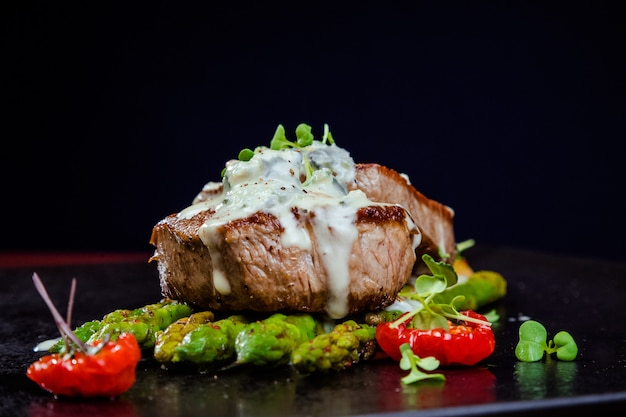 Veal medallions with asparagus garnished with white sauce