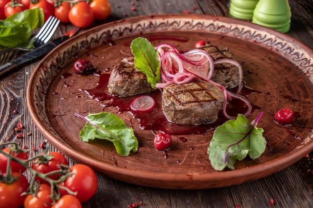 Медальоны из телятины с вишневым соусом, подается с маринованным луком и редисом, изысканное блюдо, крупный план, горизонтальная ориентация